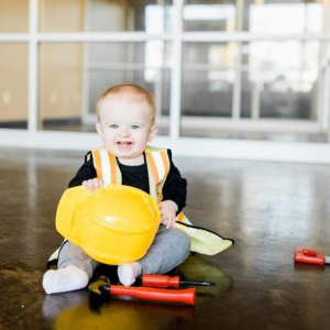 A baby wears a construction vest and grips a yellow hard hat with tools sitting in front of him.