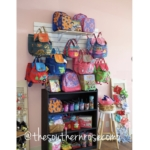 Hooks on a wall are filled with colorful purses and a bookshelf is lined with accessories.